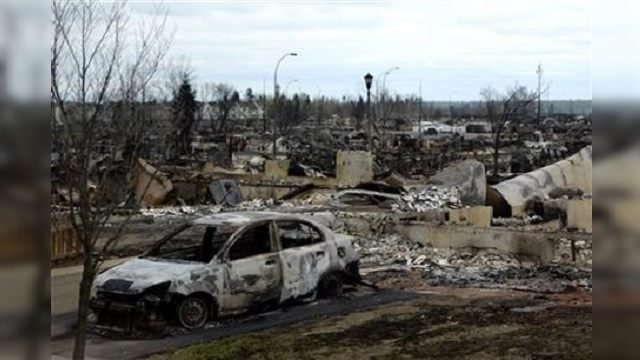 A burned out car and houses from the Alberta wildfire_281887