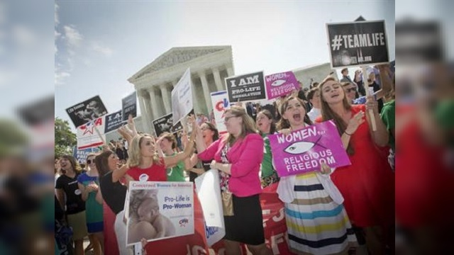 Demonstrators react to hearing the Supreme Court's decision on the Hobby Lobby birth control case outside the Supreme Court in Washington._283876