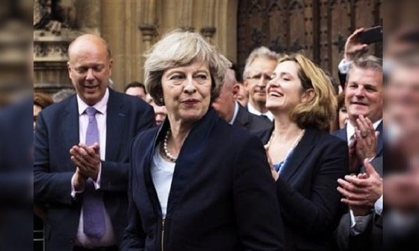 Britain's Theresa May is applauded by Conservative Party members of parliament outside the Houses of Parliament in London_298587