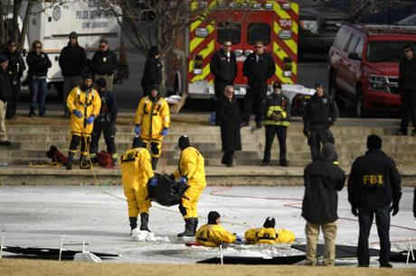 A rescue dive team removes the body of a child found in a frozen pond in Olympic Park, Tuesday, Jan. 3, 2017, in Aurora, Colo. An identification has not been made yet, but authorities notified David Puckett's family because of suspicions the body...