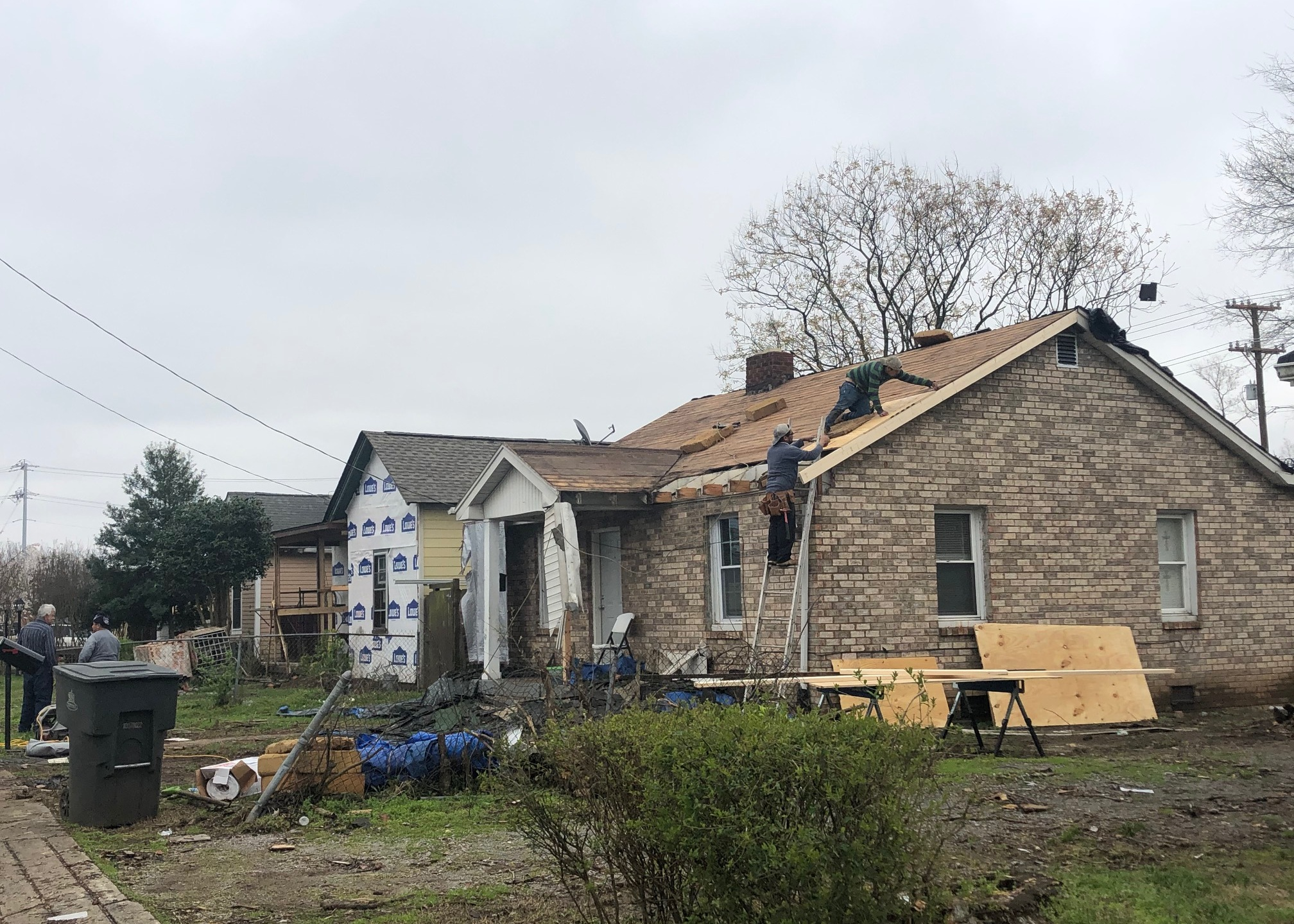 Construction crew repairs a home hit by the tornado