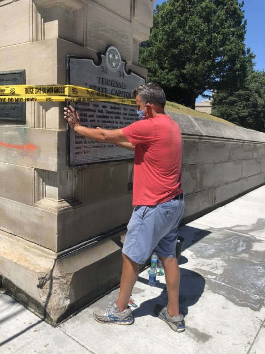 Rep Jason Powell of Nashville cleans name plate