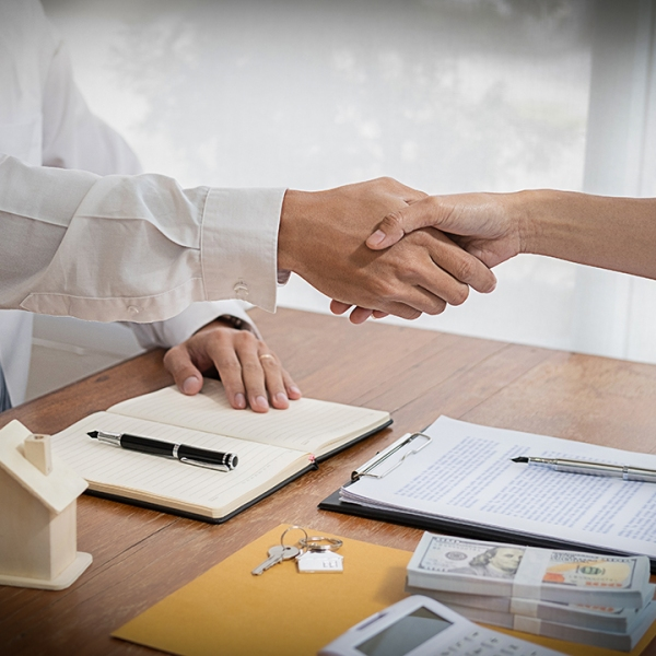 Real estate agent shaking hands with customer for deal contract