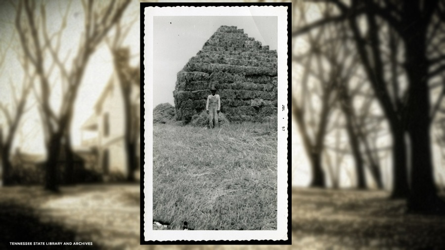 Frank Morton standing in front of hay